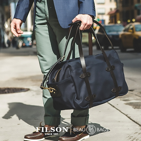 Filson Duffle Medium 11070325 Navy, man in suite wearing Filson Duffle Medium